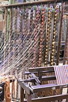 Woosh of filmy threads from columns of stacked, brightly coloured wooden bobbins in traditional jacquard weaving manufacture, La Manufacture de Roubai...