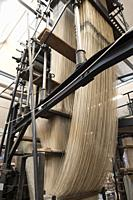 Epic cascades of thread, resembling a galleon ship in full sail, supported by wood and metal architecture of industrial revolution jacquard textile in...