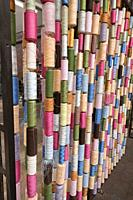 Vertical columns of vibrantly coloured thread standing sentinel like an architectural installation in traditional jacquard texile industry, La Manufac...