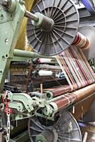 Spoked industrial cylinders feeding brightly coloured yarns into a jacquard weaving loom, La Manufacture de Roubaix, France.