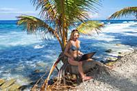 woman in bikini sitting with laptop on a palm tree. Fuvahmulah island, Indian Ocean, Maldives, Asia