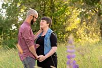 Man and a pregnant woman in a field in Oregon while the girl is in her third trimester. The couple is married and this husband and wife are expecting ...