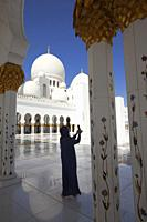 Visitor taking photos between the gilded columns of Sheikh Zayed Bin Sultan Al Nahyan Mosque, Abu Dhabi, United Arab Emirates, Middle East.