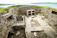 Skara Brae Stone Age Neolithic village at Skaill, Orkney, Scotland. Interior, box beds, hearth and dresser 3100 BC. House 1 with Bay of Skaill behind.