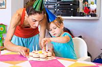 three years old blonde child and woman with colored cone caps, at birthday party, putting candles in flower-shaped cake on colorful tablecloth at home...