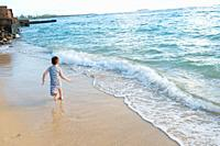 Five year old boy playing in the waves of the Pacific Ocean and having fun while on vacation in Oahu Hawaii.