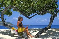 young woman sitting on a heart shaped tree on a beach of Palm Island, Grenadines islands, Saint Vincent and the Grenadines, Winward Islands, Lesser An...