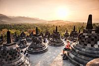 Tourists enjoying sunset over unroofed pyramid of Borobudur Temple, crowned by bell-shaped stone domes (Magelang Regency, Central Java, Indonesia).