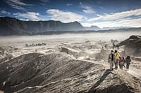 Tourists walking towards Bromo's caldera in Bromo Tengger Semeru National Park (East Java, Indonesia).