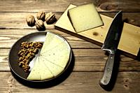 portion and slices of spanish manchego cheese on cutting board with nuts and kitchen knife on wood background.