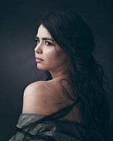 Beautiful plus size model posing at camera, dramatic female portrait.
