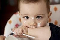 Toddler Sitting in Highchair and Eating Yogurt. Baby Learning to Eat and Has Yogurt on Face