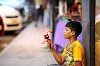 Bangalore, India - October 16, 2016: Unknown kid sitting aside a shop spotted playing with his toy in Brigade Road, Bangalore.