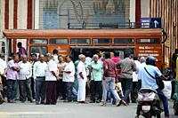 Bangalore, India - October 23, 2016: Large group of people buying hot coffee from a mobile canteen while other stand aside in the Avenue road.