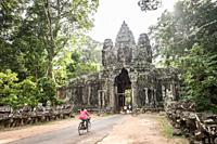Young cambodian girl biking east gate of Angkor Thom compound (Siem Reap Province, Cambodia).