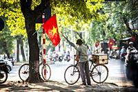 Vietnamese man close Vietnam flag in Hanoi.