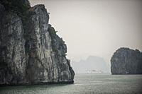 Tourists vessel between islands in the karst landscape of Ha Long Bay, Quang Ninh Province, Vietnam. Ha Long Bay is a UNESCO World Heritage Site.