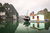 Fishing boat and traditional house in karst landscape of Ha Long Bay, Quang Ninh Province, Vietnam. Ha Long Bay is a UNESCO World Heritage Site.