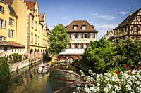 Tourists boat along channel at Little Venice in medieval town of Colmar, Alsace (department of Haut-Rhin, region of Grand Est, France).