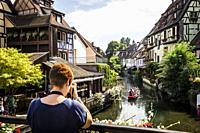 Taking pictures of tourists boat along channel at Little Venice in medieval town of Colmar, Alsace (department of Haut-Rhin, region of Grand Est, Fran...