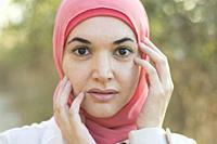 Beautiful Muslim woman wearing Hijab hands touching face.