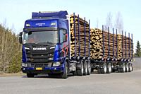 Blue Scania R730 XT logging truck makes left turn on test drive during Scania Tour Turku 2018 in Lieto, Finland - April 12, 2018.