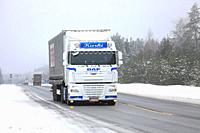 Beautifully customized DAF XF 105 truck of J Kurki hauls Freja cargo trailer along highway in winter in Raasepori, Finland - February 9, 2018.
