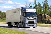 Ice blue Next Generation Scania S500 semi trailer delivers load along E18 motorway in South of Finland on a beautiful day of summer. Paimio, Finland -...