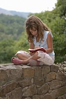 girl writing a diary in the field, Asturias, Spain.