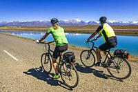 Cycling under the Southern Alps along the Tekapo Canal, Lake Tekapo, Canterbury, South Island, New Zealand.