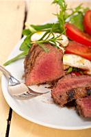 beef filet mignon grilled with fresh vegetables on side ,mushrooms tomato and arugula salad.