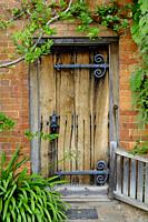 Old wooden front door with large ornate hinges.