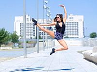 young ballerina dances and jumps on the street of a city. In Zaragoza, Aragón, Spain.