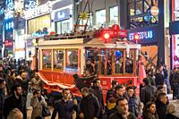 Passengers grip onto the sides of trolley car as it makes it way through the crowded streets of Istanbul, Turkey.