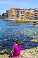 A preteen all dress in pink playing on the side of the bay of Saint Tropez. We can see the city village of Saint Tropez in France behind her.