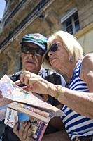Older mature retired couple looking at a map trying to figure out their way in the streets of the city of Marseille.