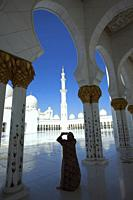Visitor with headscarf taking photos between the gilded columns of Sheikh Zayed Bin Sultan Al Nahyan Mosque, Abu Dhabi, United Arab Emirates, Middle E...