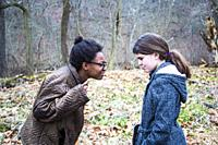 Two teens/ Pre-teens arguing. One African American teen girl, yelling and correcting her caucasian friend/sister. She is bossing her around, pointing ...