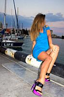Beautiful seated woman in the shore of the port in Yalta, Crimea.