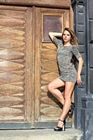 Sexy and elegant Ukrainian woman wearing a leopard skin print outfit posing standing and reclining to one side in front of a large wooden door for a p...