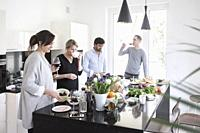 Group of friends preparing food together. Casually chatting , snacking , laughing and enjoying themselves in modern kitchen.
