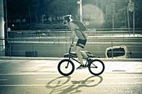 Young man riding a BMX bicycle style. Barcelona, Catalonia, Spain.