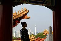 Malaysia, Selangor State, Kuala Lumpur, woman at Thean Hou Chinese Temple, KL tower (Menara Kuala Lumpur) in the background, Model Released