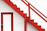 Abstract image of a red stairway against a white wall. British Columbia, Canada.