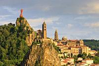 Statue of Notre Dame de France with Saint Michel d'Aiguilhe Chapel and Notre Dame Cathedral Le Puy en Velay Haute-Loire Auvergne-Rhône-Alpes France.