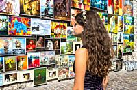 Girl looking at the paintings exhibited in the Medieval Fortification, Krakow, Poland.