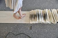 A side view from the knees down of a woman artist in a white dress turning as she creates a performance art work at an artist run gallery in Windsor, ...