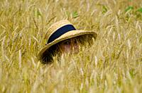 Woman in the Wheat Field with a Straw Hat and Looking in Locarno, Switzerland.
