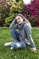 16 year old teenager sitting in a park with grass and flowers, taken in Limoges, France.