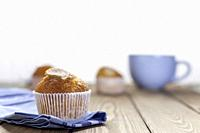 muffin cupcake on blue napkin and blue cup on wood table and white background.